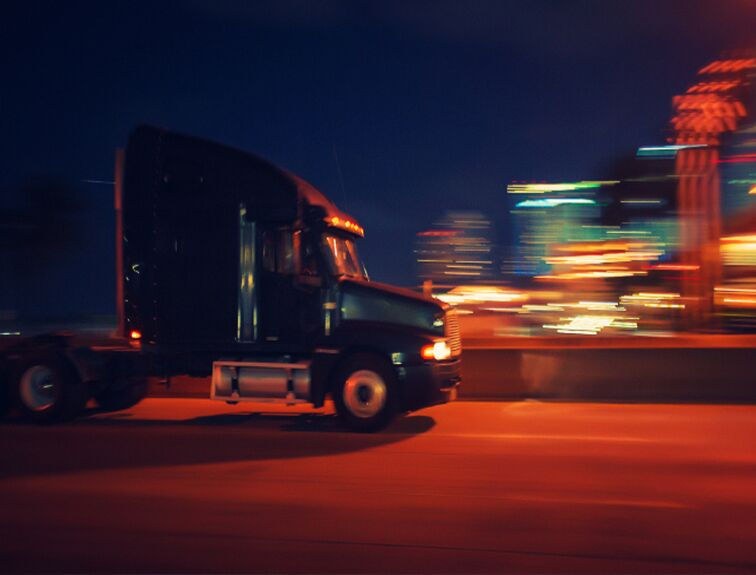 semi truck driving in the city at night