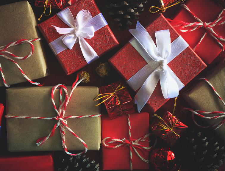 Image of Christmas gifts wrapped in red, brown and gold paper with bows