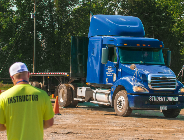 Image of a student driver in blue CDL truck with instructor watching