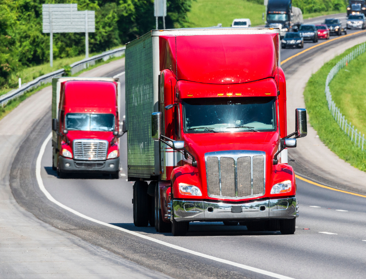 two red semi trucks driving down interstate