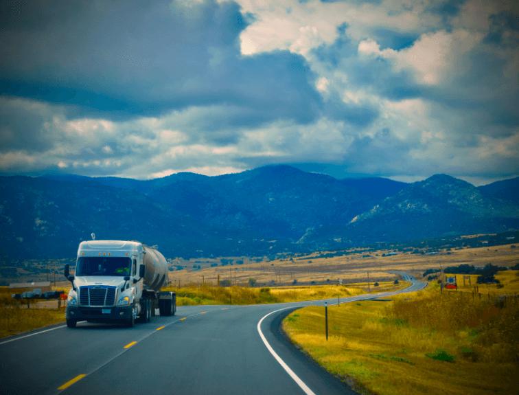 White Tanker Truck leaving the mountains on left side